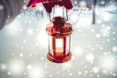 Trzymający czerwoną świeczkę latarniowa w zima lesie Obraz Stock