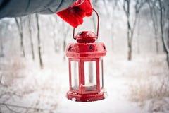 Trzymający czerwoną świeczkę latarniowa w zima lesie Obrazy Royalty Free