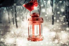 Trzymający czerwoną świeczkę latarniowa w zima lesie Obraz Royalty Free