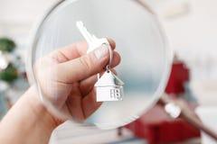 Trzymający domów klucze na domu kształtował keychain zbliżenie koncepcja real nieruchomości Obrazy Stock
