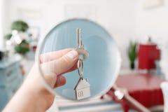 Trzymający domów klucze na domu kształtował keychain zbliżenie koncepcja real nieruchomości Obraz Stock