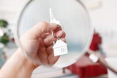 Trzymający domów klucze na domu kształtował keychain zbliżenie koncepcja real nieruchomości Zdjęcia Royalty Free