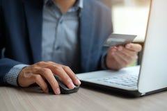 Trzymający kredytową kartę i używać laptop dla online zakupy podczas gdy robić rozkazowi zdjęcia stock
