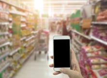Trzymający mądrze telefon odizolowywający nad białym tłem - mockup zdjęcie stock