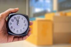 Trzymający zegar na miasto zamazującym tle czasu 8:00 jest lub pm zdjęcie royalty free