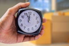 Trzymający zegar na przemysł zamazującym tle czasu 12:00 am o Obraz Stock