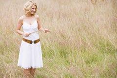 trzymaj trawę na zewnątrz uśmiechać czas trwania kobiety Obraz Stock