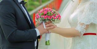 Trzymali różowego kwiatu bukiet w ich rękach ręki składali za ich plecy, trzymają pięknego małego ślubnego bukiet wzrastali Zdjęcie Stock