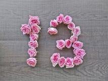 13, trzynaście - rocznik liczba różowe róże na tle ciemny drewno fotografia royalty free
