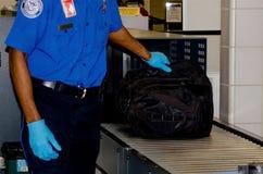 TSA manipulant un sac Photos libres de droits