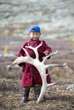 Tsaatan boy, dressed in a traditional deel with a reindeer horn Royalty Free Stock Photos