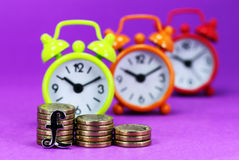 Tsaking A Pounding. A Silver Pound sign in front of three piles of Golden coins, with three traffic light colored clocks in the very background, indicating is it Royalty Free Stock Photography