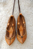 Tsarvuli. Pair of traditional Bulgarian leather shoes agaisnt white lambskin background Stock Image