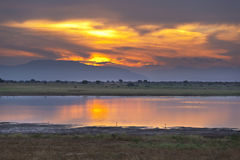 Tsavo East Lake Sunset. Sunset and lake in Tsavo East National Park in Kenya with an elephant in the background Royalty Free Stock Photo