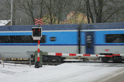 Tschechischer Bahnübergang am Winter mit Zug in einem Schneesturm Stockfotos