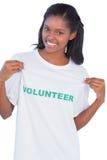 Tshirt voluntário vestindo da jovem mulher e apontar-lhe Imagem de Stock Royalty Free