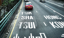 Tsim Sha Tsui, Hong Kong typogrohy on  road with red classic taxi Royalty Free Stock Image