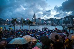 Crowded people waiting National Day Fireworks Display in rain at waterfront of Victoria Harbour of Hong Kong Stock Photos