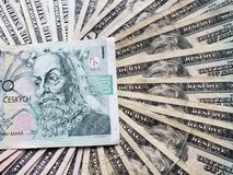 Tsjechisch bankbiljet van korun 100 en achtergrond met Amerikaanse dollarsrekeningen
