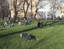 Tsjechische Republiek, Praag, 10 April, 2018: slaapmens en groep mensen die op weelderig groen gras ontspannen en van de vroege l Stock Foto