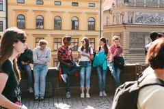 Tsjechische Republiek, Praag - 29 09 2017 De groep het diverse jongeren koelen cobblestoned riverfront in zonnige dag stock foto