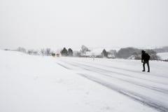 Tęsk spacer wzdłuż śnieżnej drogi. Fotografia Royalty Free