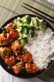 Tso κοτόπουλο με το ρύζι, τα κρεμμύδια και την κινηματογράφηση σε πρώτο πλάνο μπρόκολου κάθετο τ Στοκ Φωτογραφίες