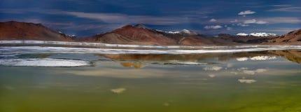 Tso Kar高盐湖的全景照片在一夏天无风天:水表面作为镜子反射山, 免版税库存照片