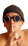 Tssss!. Young male in black hat and goggles tells you to keep quiet stock photo