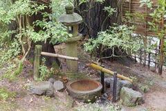 Tsukubai-Wasser-Brunnen und Stein-Laterne im japanischen Garten Stockbild