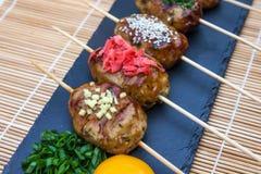 Tsukune - de Japanse die vleesballetjes van kippenyakitori met Spaanse pepersaus, vlokken, grondpeper en citroenwiggen worden ged stock afbeelding