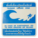Tsunami hazard zone warning sign. Posted along the beaches and coastline of thailand with text in case of earthquake go to high ground or inland in engliah and Stock Photo