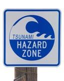 Tsunami Hazard Zone warning sign isolated. Tsunami Hazard Zone warning sign on an old wood post isolated on white background stock photo