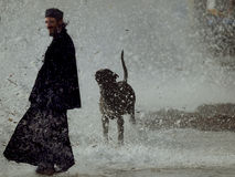 Tsunami at Mount Athos. A Greek orthodox monk is being surprised by a sudden gigantic wave in the stormy harbour of Ouranoupolis, border station for the monks Stock Images