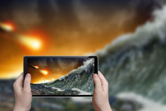 Tsunami photograph. Abstract tablet pc in hands photographs giant tsunami waves crashing small coastal town and asteroid impact royalty free stock image