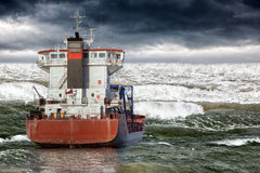 Tsunami on sea. Cargo ship during storm in ocean Royalty Free Stock Image