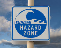 Tsunami Warning Sign. With a cloud filled sky Stock Image