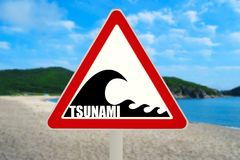Tsunami Warning Sign. Tsunami hazard zone sign on the beach (Shallow DOF Royalty Free Stock Images