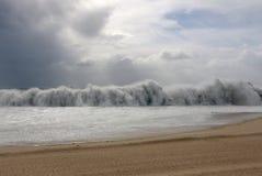 Tsunami wave during a storm. A big stunami wave splashing near a beach shore Royalty Free Stock Photo