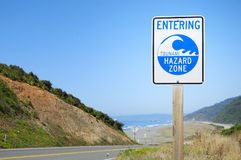 Tsunami Zone. Tsunami warning zone road sign near ocean beach Royalty Free Stock Image