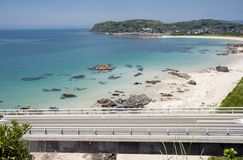 Bridge over the coast. Tsunoshima Ohashi bridge over the sandy beach and shallow sea unser sky Royalty Free Stock Images