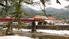 TSUWANO, JAPAN - NOVEMBER 28.2018: Bezoekers die een beeld wachten te nemen van het rode trein doornemen een brug in tsuwano terw stock afbeeldingen