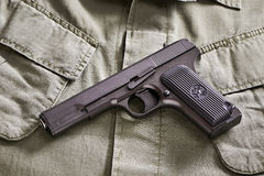 TT russian pistol and belt lie on military jacket Royalty Free Stock Photography