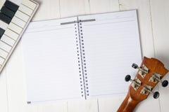 Tête de guitare et mini clavier sur un livre pour l'écriture de chanson Photographie stock