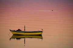 Little boat floating on the calm water under amazing sunset in Q. Ttle boat floating on the calm water under amazing sunset in Quellon, Chiloe Island in Chile stock photo