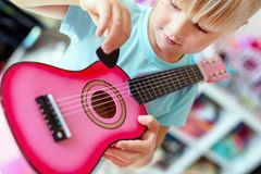 Little cute blond girl having fun learning to play small ukulele guitar at home.Toddler girl trying to play toy musical instrument royalty free stock photo