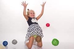 Ttle girl playing with colored balls Royalty Free Stock Photos