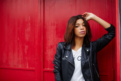 Аttractive black female posing on red wall background in the city Stock Images