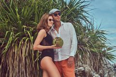 Attractive couple, holds coconut with a tube, posing on a beach near palm bush, enjoys a vacation on a beautiful island. An ttractive couple, holds coconut with Stock Image