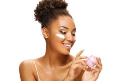 Аttractive girl using moisturizing cream. Photo of smiling african american girl on white background. Beauty & Skin care concept stock image